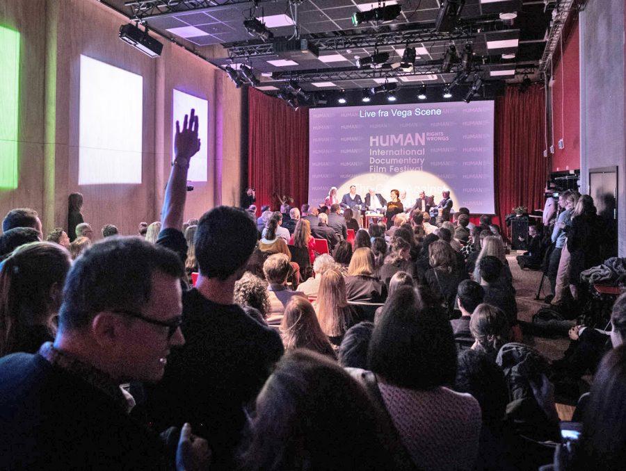 bilde av folkemengde som sitter med ryggen til og ser mot en scene med mennesker på paneldebatt.