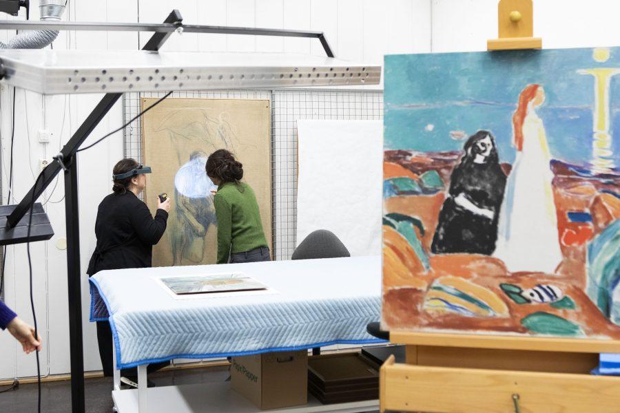 Bilde i forgrunnen, i bakgrunnen ser man to kvinner lyse på et Munchbilde.