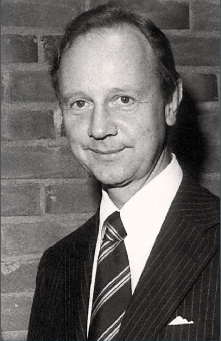 sort hvitt bilde, mann i dress med slips smiler og ser rett inn i kameraet.