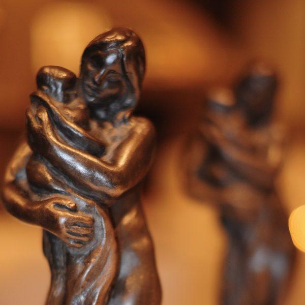Bilde av to like og små bronsestatuetter som fremstiller en kvinne som holder et barn. Den ene i forgrunnen er skarp, mens den i bakgrunnen er uskarp.