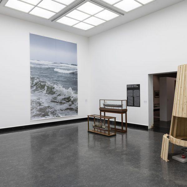 Bilde fra et hjørne av et utstillingsrom. På den hvite veggen til venstre henger to bilder  og på den andre veggen finnes to montre som viser gjenstander og en større tre struktur.