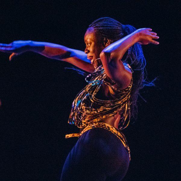To dansere på scenen, en i bakgrunnen, mens kvinnen i forgrunnen er skarp. Hun ses i profil fra hoftene og opp, mens hun danser.