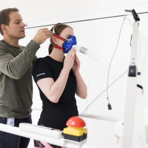 Bilde av mann med kort hår som tar på kvinne en maske. Masken er koblet til et hvitt rør. Rundt dem er medisinsk utstyr.