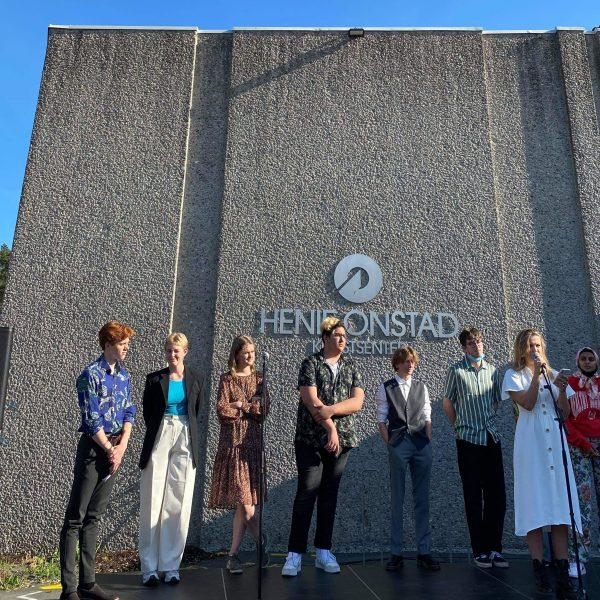 Ni ungdommer stående på scene foran Henie Onstad Kunstsenter