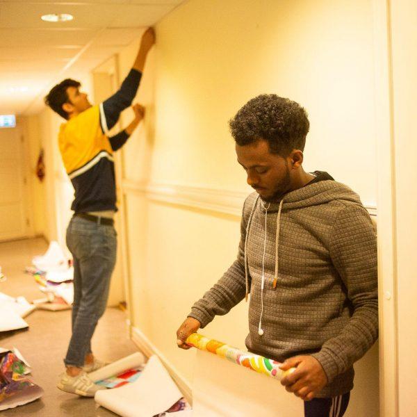 To gutter som jobber med oppheng av plakater på vegg.