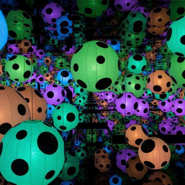 Bilde av Kusama sin kunstinstallasjon. Veggene og gulv er dekket med speil som reflekterer lyslyktene som er i forskjellige farger med sorte prikker og som henger i rommet.