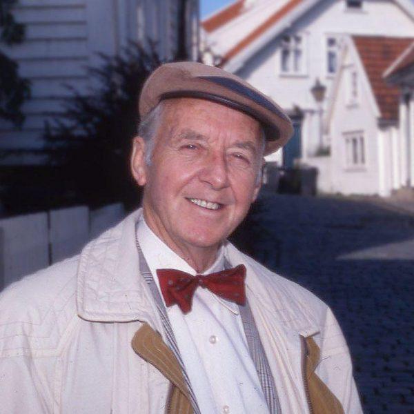Mann stående i en gate med hvite trehus. Han smiler og ser inn i kamera, med sixpence på hodet og har på seg en hvit skjorte og rød sløyfe.